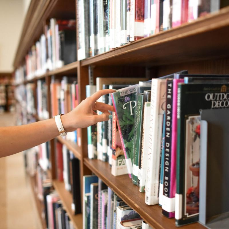 hand grabbing book from library